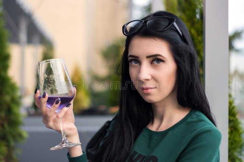 Den unga kvinnan med ett exponeringsglas av den violetta coctailen sitter på på sommarterrassen av restaurangen royaltyfri bild