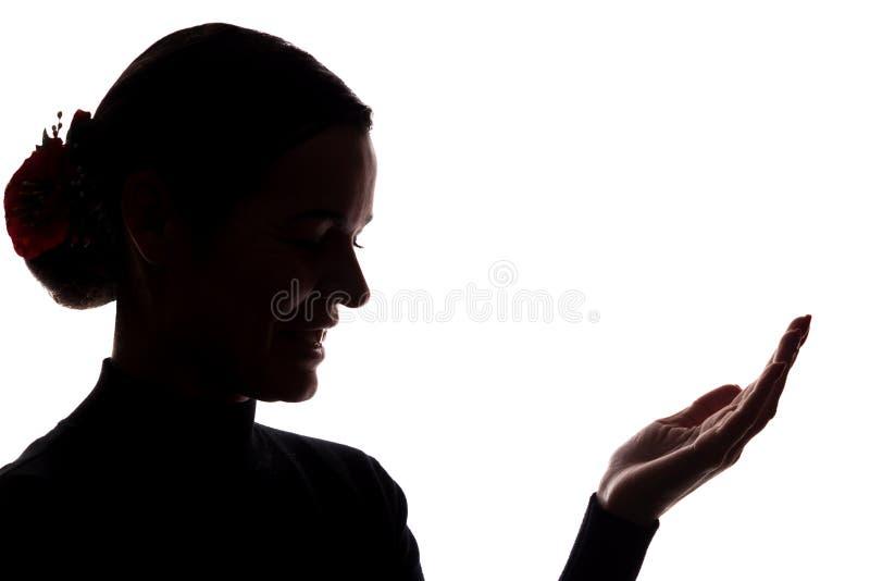 Den unga kvinnan med ett leende visar hans hand fram?triktat arkivbild