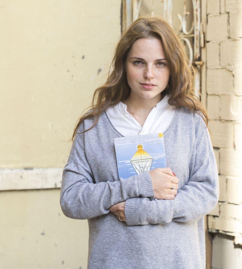 Den unga kvinnan med framsidan med fräknar och med boken i hennes händer står opposite av en grå vägg royaltyfri fotografi