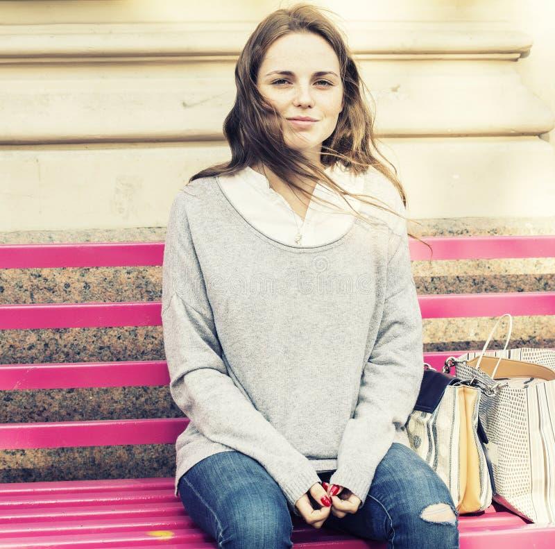 Den unga kvinnan med framsidan med fräknar placerar på en bänk Oavkortade mans för utomhus- bild längd fotografering för bildbyråer