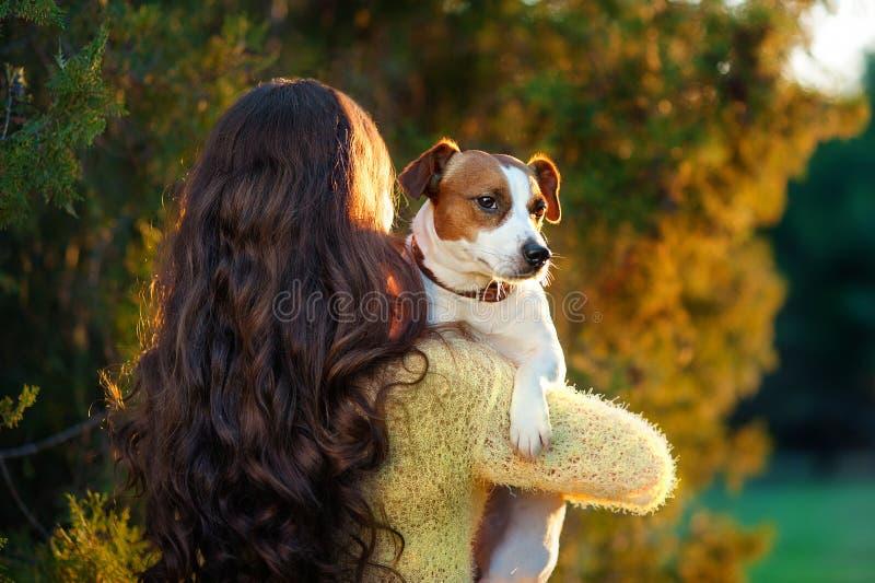 Den unga kvinnan med härligt långt hår står med henne tillbaka och rymmer en Jack Russell terrier på hennes skuldra in royaltyfria bilder