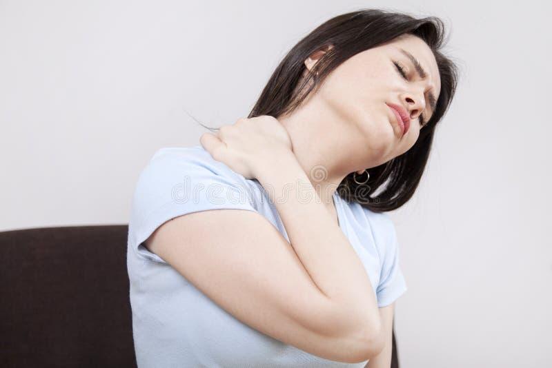 Den unga kvinnan med halsen smärtar arkivfoton