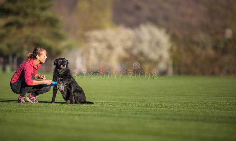 Den unga kvinnan med hennes svarta hund som är utomhus-, i, parkerar att spela frisbeen royaltyfria bilder