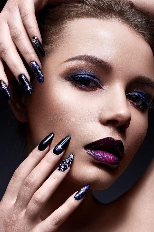 Den unga kvinnan med idérikt smink och violetta kanter med en lutning och mousserar på framsidan Den härliga modellen med ljust s royaltyfria foton