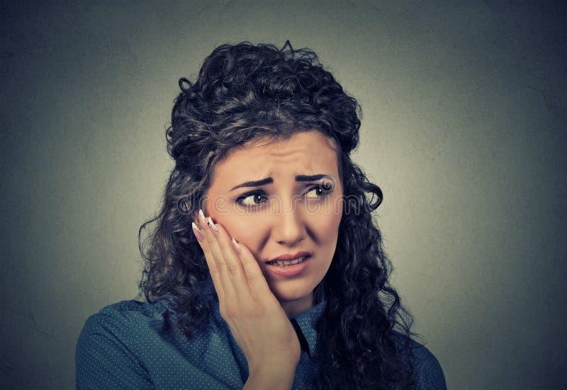 Den unga kvinnan med känsligt tandvärkkronaproblem till skrik från smärtar omkring arkivfoton
