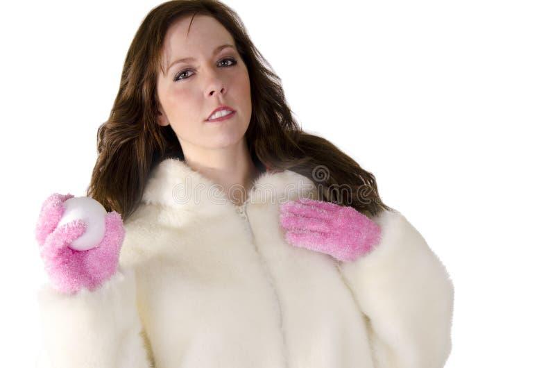 Den unga kvinnan med kastar snöboll royaltyfri bild