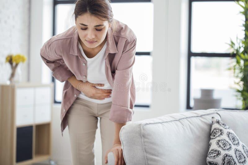 Den unga kvinnan med magen smärtar
