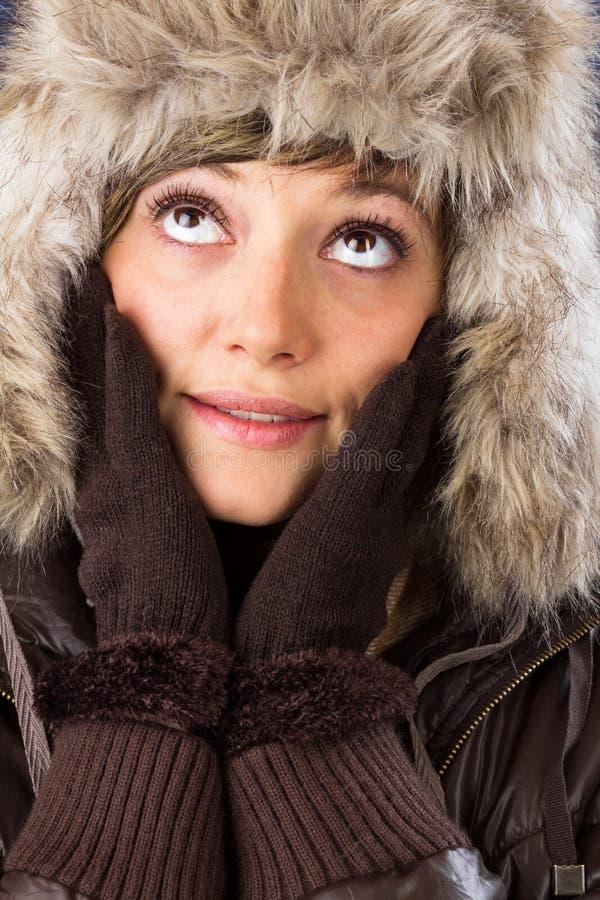Den unga kvinnan med pälshatten och handskar ser upp arkivfoto