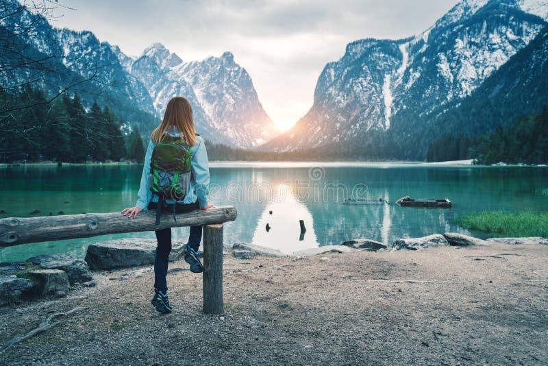 Den unga kvinnan med ryggsäcken sitter på kusten av sjön royaltyfri foto