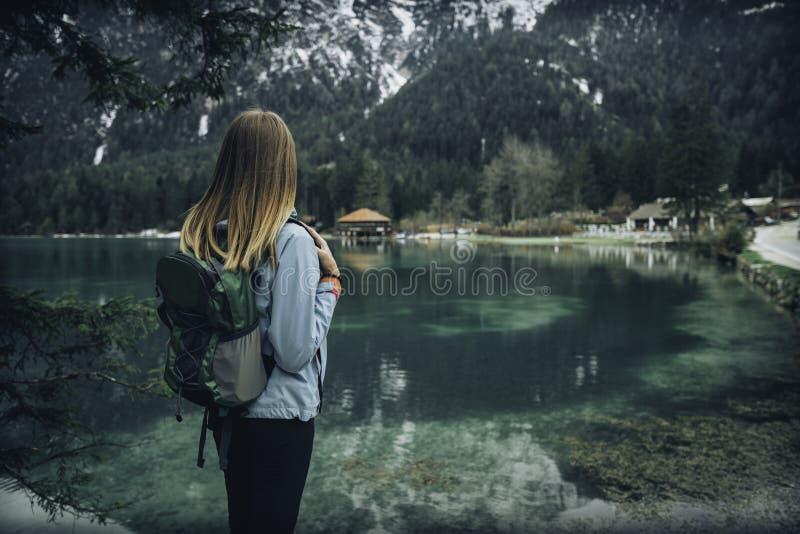 Den unga kvinnan med ryggsäcken står på kusten av sjön arkivfoto