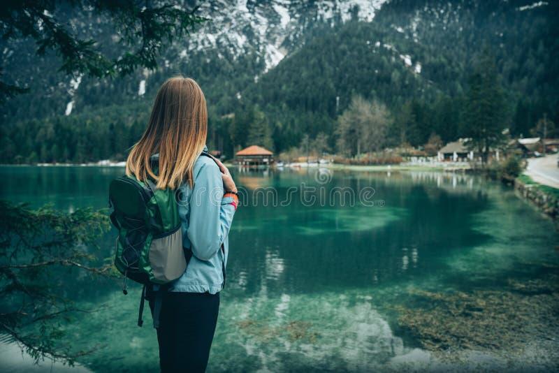 Den unga kvinnan med ryggsäcken står på sjön arkivfoto