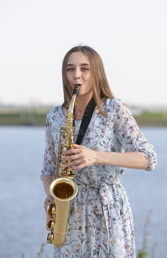 Den unga kvinnan med saxofonen i parkerar royaltyfri bild