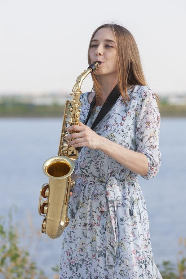 Den unga kvinnan med saxofonen i parkerar arkivfoton