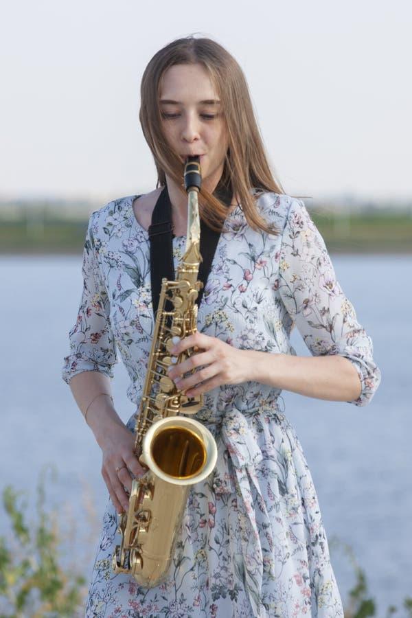 Den unga kvinnan med saxofonen i parkerar royaltyfria foton