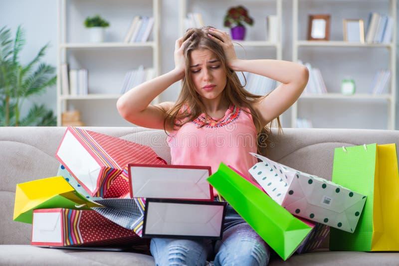 Den unga kvinnan med shoppingpåsar returnerar inomhus på soffan arkivfoto