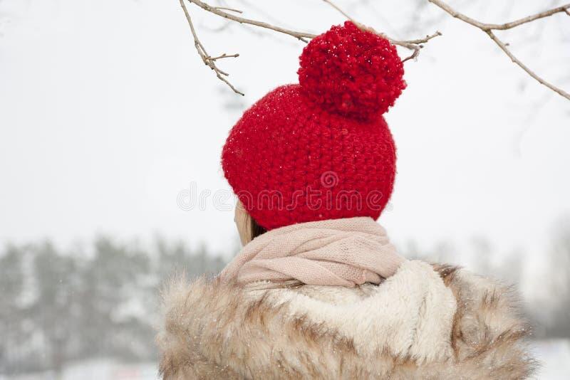 Den unga kvinnan med själv virkade den röda ull- hatten som var utomhus- arkivbild