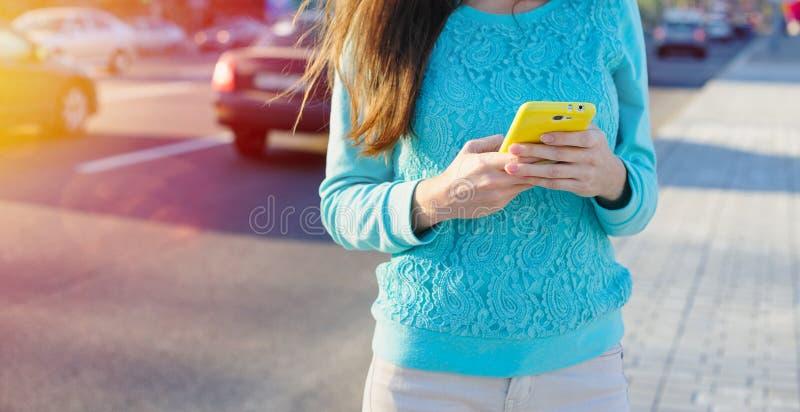 Den unga kvinnan med smartphonen skriver royaltyfri fotografi