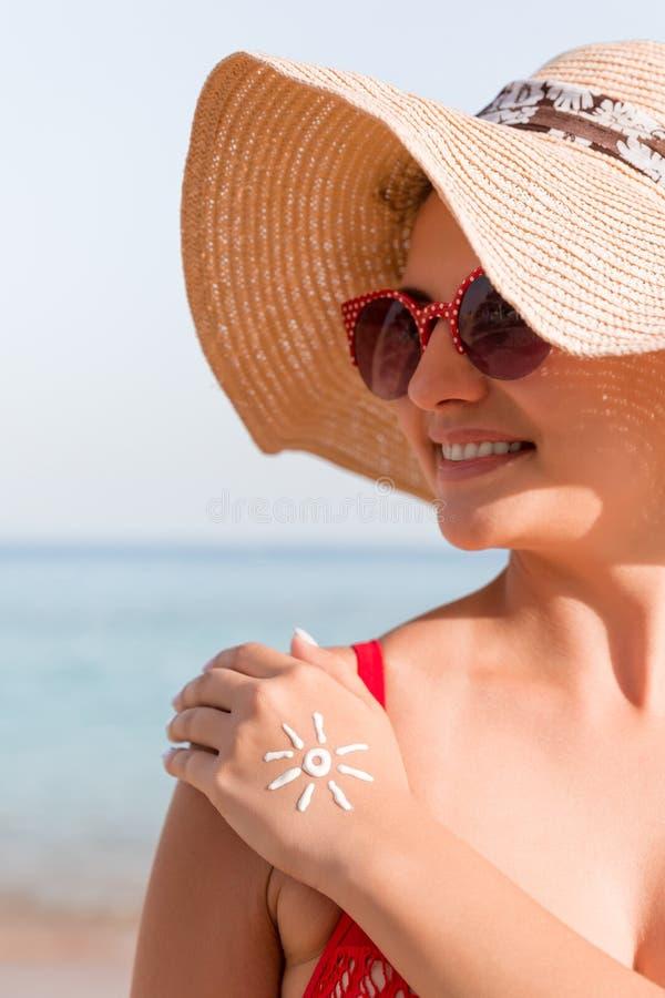 Den unga kvinnan med solform p? hennes hand - gjorde av sunscreen p? stranden arkivfoto