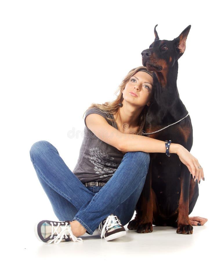 Den unga kvinnan med svart dobermann förföljer royaltyfria bilder
