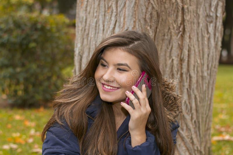 Den unga kvinnan med telefonen i höst parkerar arkivbilder