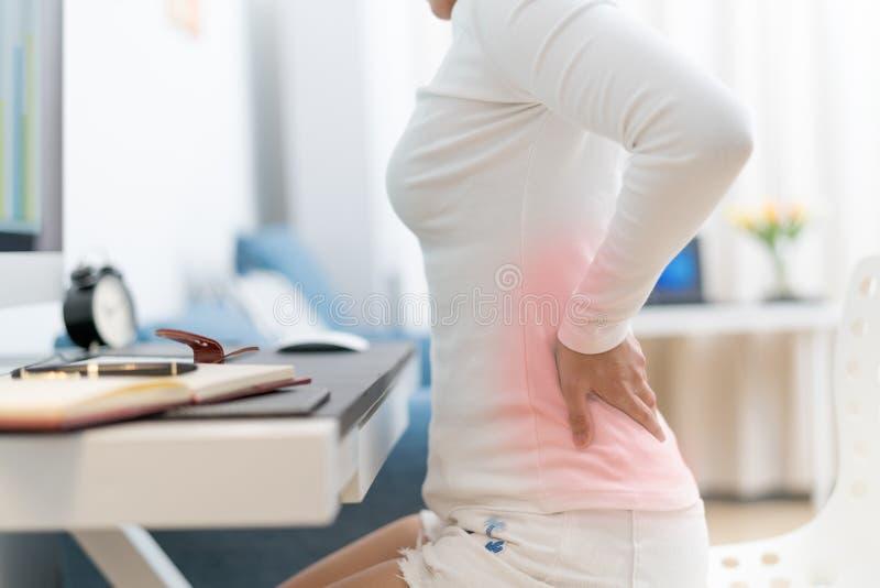 Den unga kvinnan med tillbaka smärtar arbete med datoren Sjukvård- och läkarundersökningbegrepp royaltyfri bild