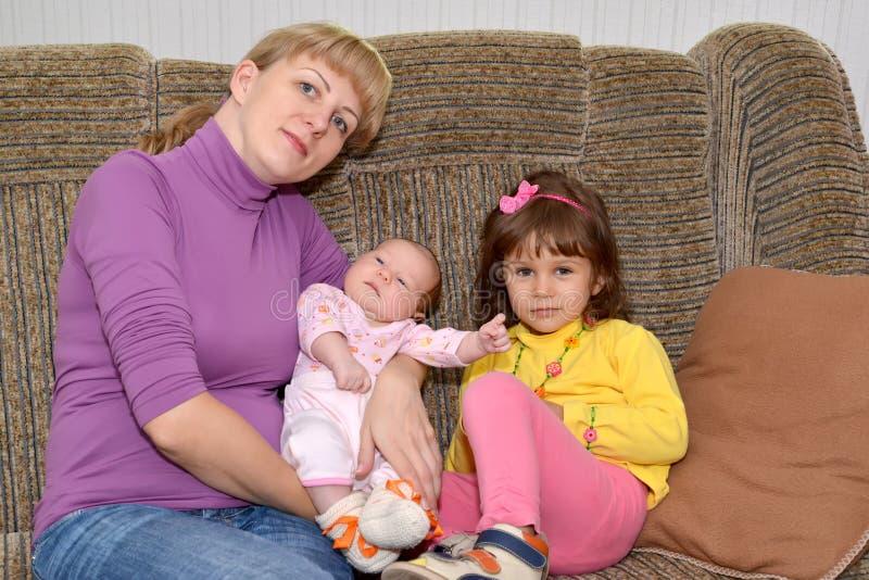 Den unga kvinnan med två småbarn 3 flickor för kamerasoffafamilj se sitting för orange stående för moder deras beträffande där royaltyfri foto