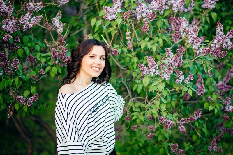 Den unga kvinnan, mot bakgrund av sommargräsplan parkerar, gör grön sidor royaltyfri foto