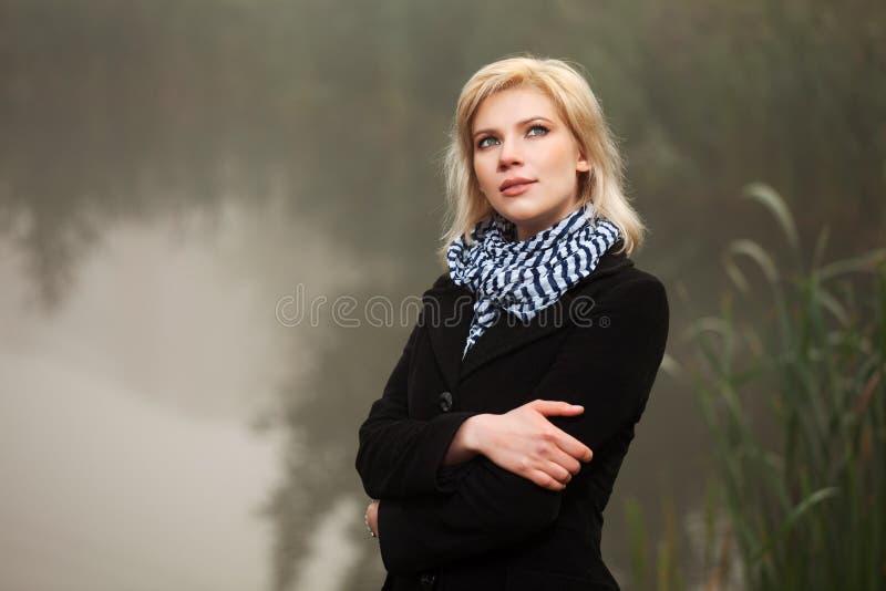 Den unga kvinnan mot ett dimmigt landskap royaltyfri fotografi