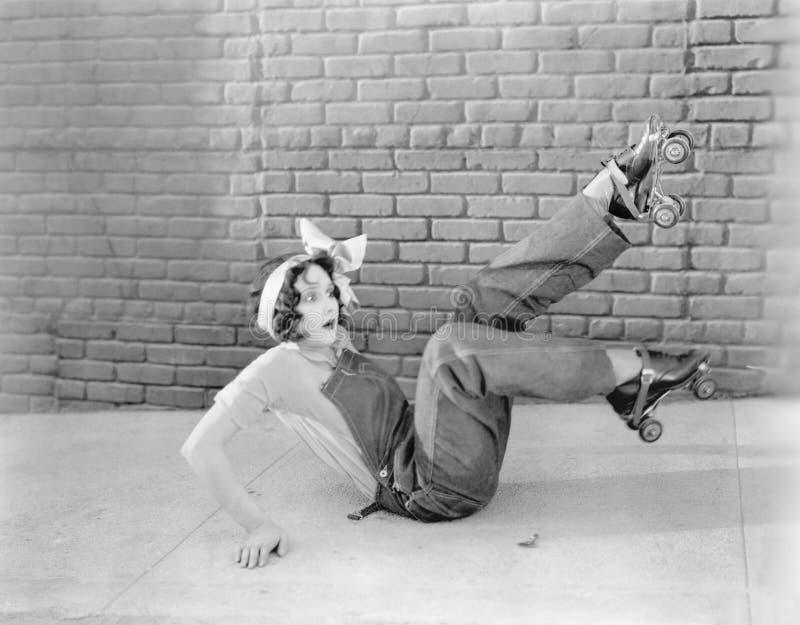 Den unga kvinnan på jordningen som ser förvånad, når han har funnit ut det åka skridskor för rulle, är ett halt ämne (alla visade fotografering för bildbyråer