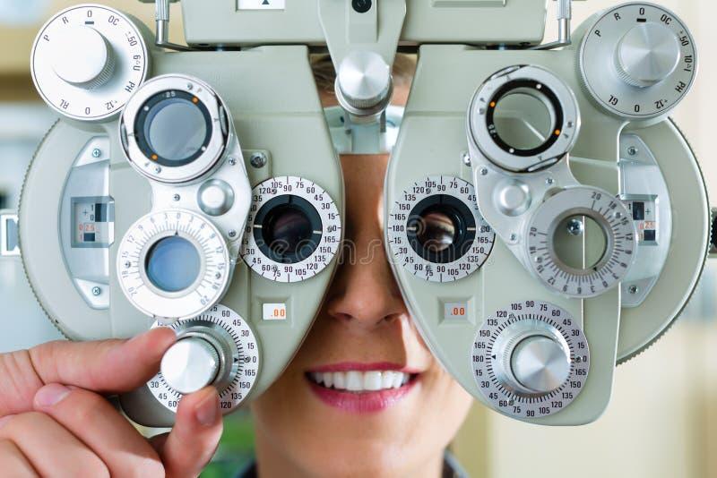 Den unga kvinnan på phoropter för synar testar royaltyfria foton