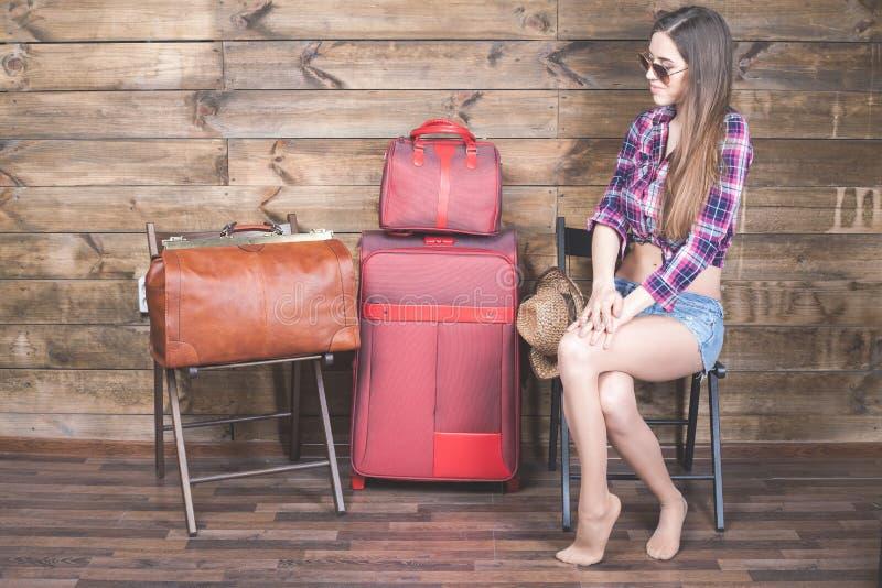 Den unga kvinnan packade redan hennes saker, kläder på bagage, resväska arkivfoto