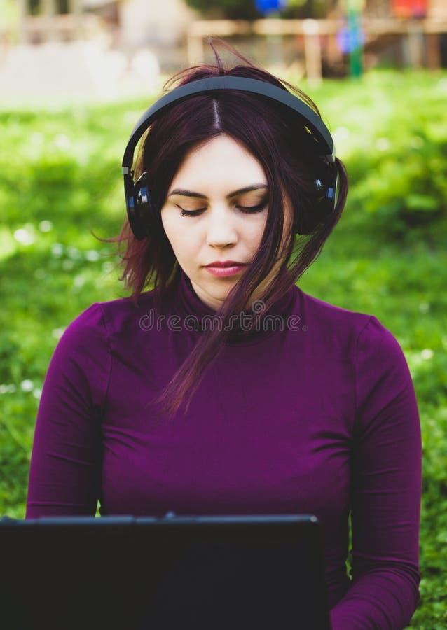 Den unga kvinnan parkerar in genom att använda lyssnande musik för bärbar datordator royaltyfria foton