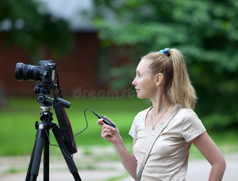 Den unga kvinnan parkerar in med kameran på en tripod arkivbild