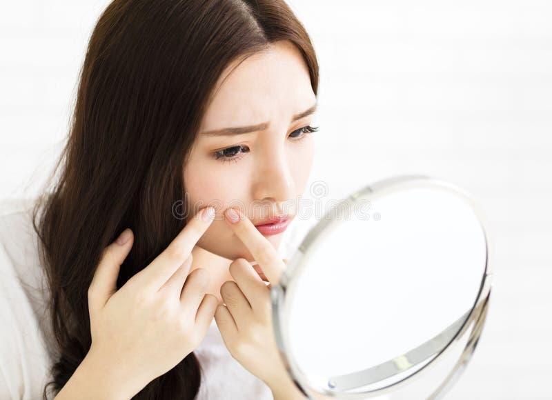 Den unga kvinnan pressar hennes akne framme av spegeln arkivfoto