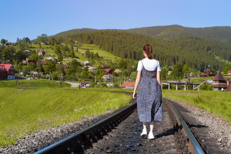 Den unga kvinnan promenerar järnvägsspåren gröna berg royaltyfri fotografi