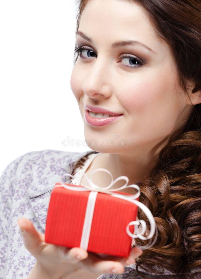 Den unga kvinnan räcker en gåva