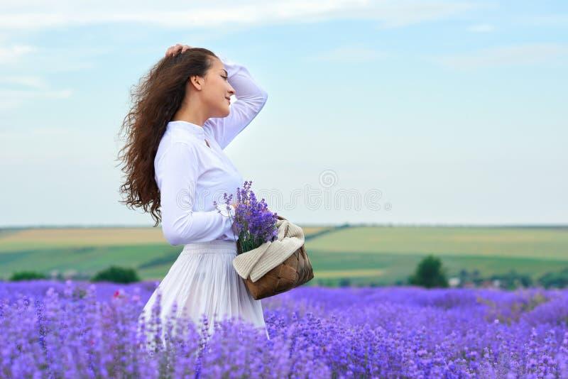 Den unga kvinnan ?r i lavendelblommaf?ltet, h?rligt sommarlandskap royaltyfria foton
