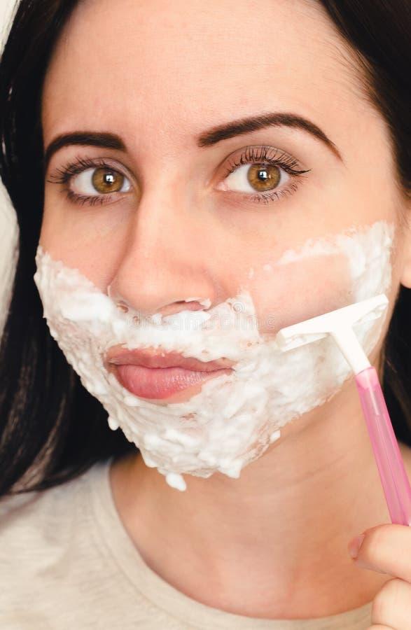 Den unga kvinnan rakar hennes mustasch och skägg med en rakkniv fotografering för bildbyråer