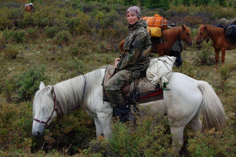 Den unga kvinnan reser till och med moutnainsna på hästrygg royaltyfria bilder