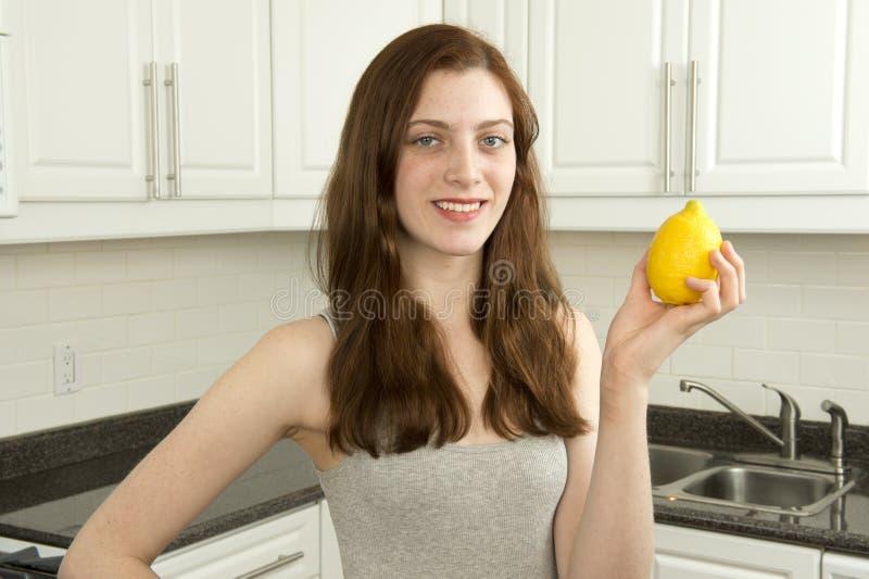Den unga kvinnan rymmer citronen arkivbild