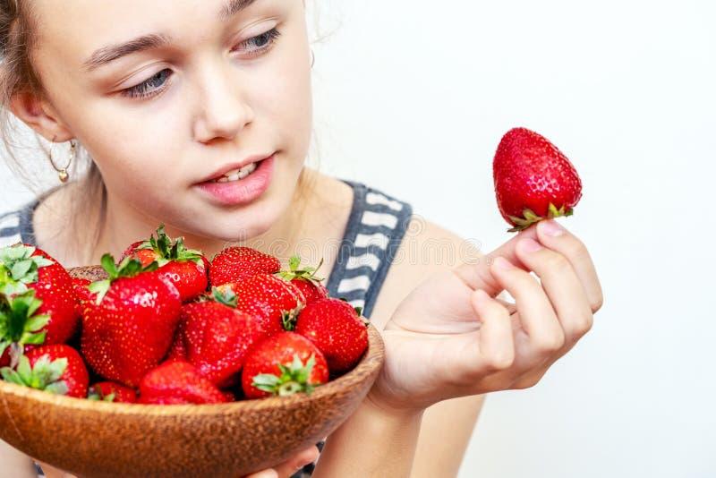 Den unga kvinnan rymmer en bunke av nya jordgubbar royaltyfri fotografi