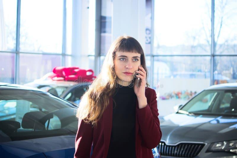Den unga kvinnan säljer bilen royaltyfria bilder