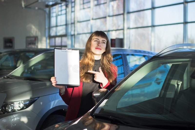 Den unga kvinnan säljer bilen royaltyfri bild