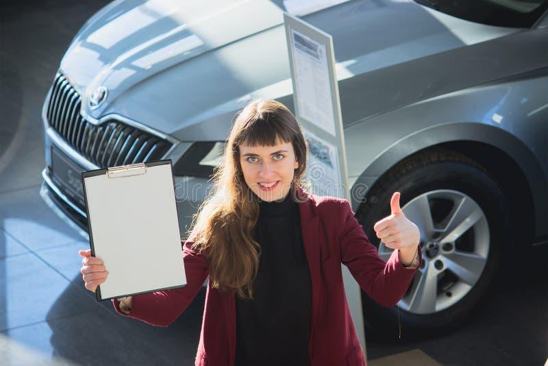 Den unga kvinnan säljer bilen arkivfoto