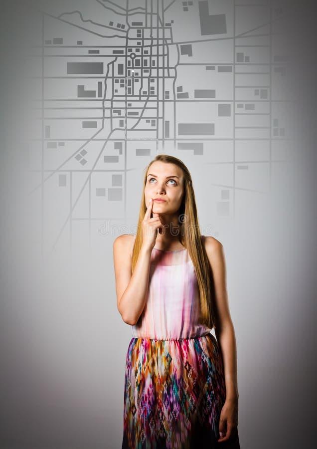 Den unga kvinnan söker efter en rutt på stadsöversikten arkivfoto