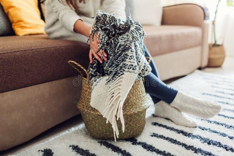 Den unga kvinnan s?tter filten i sugr?rkorg Inre dekor av vardagsrum royaltyfria foton