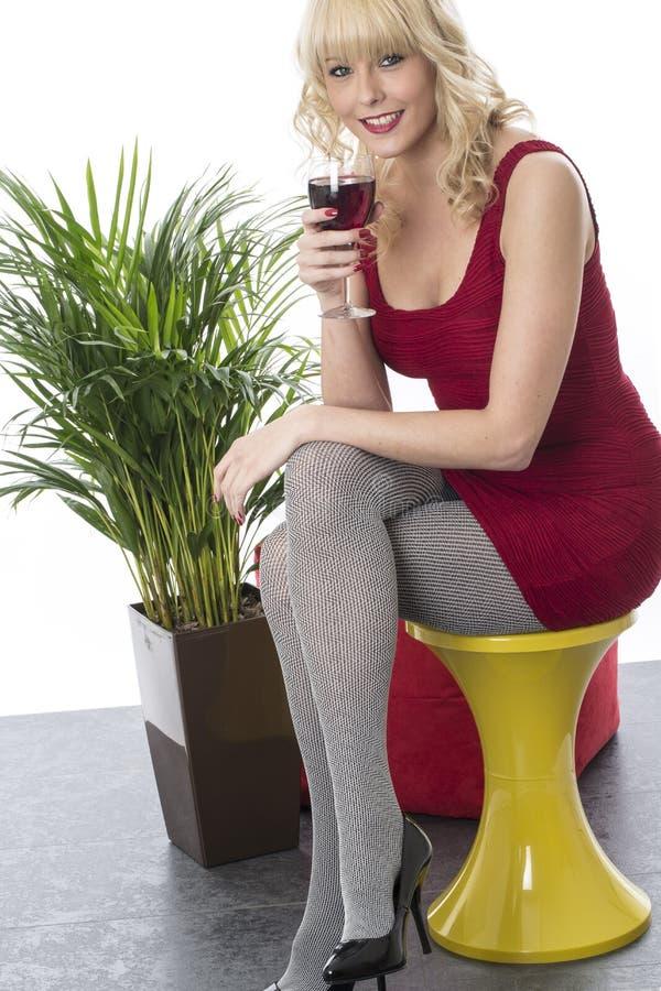 Den unga kvinnan Sat på stol lägger benen på ryggen korsat tycka om ett exponeringsglas av rött vin royaltyfri fotografi