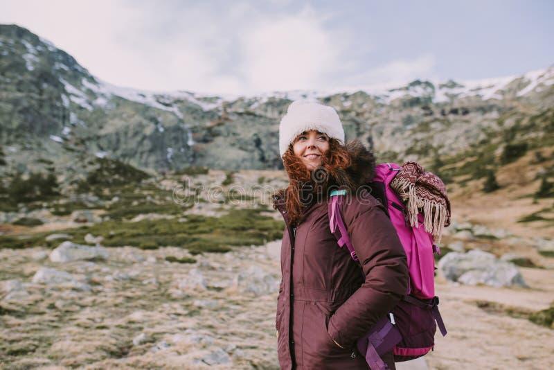 Den unga kvinnan ser långt, medan tycka om berget arkivbild