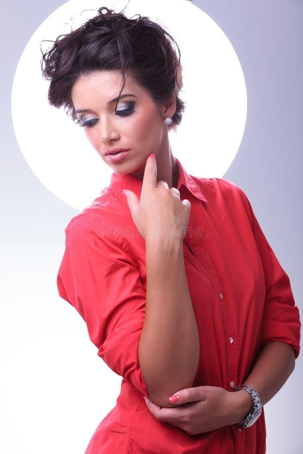 Den unga kvinnan ser ner och handlagframsidan arkivbild