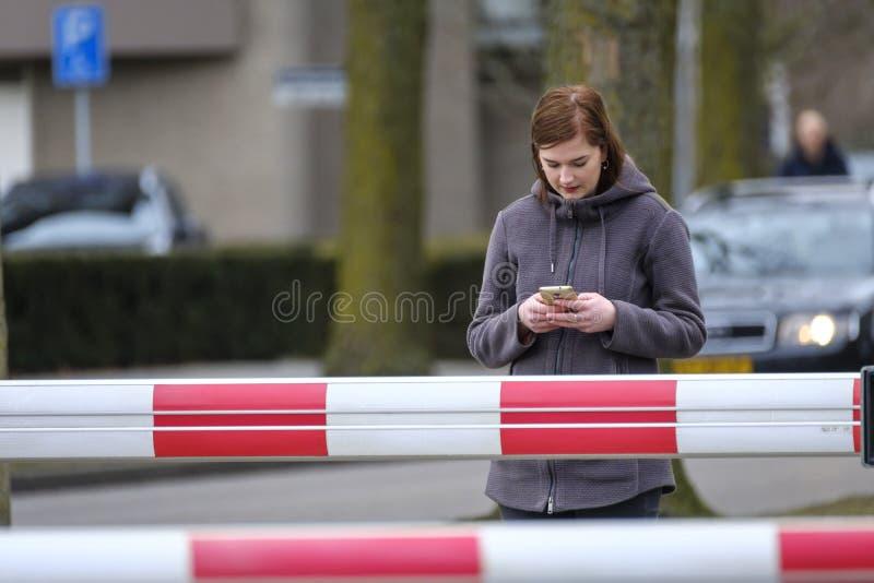 Den unga kvinnan ser på hennes mobil på en järnvägkorsning fotografering för bildbyråer